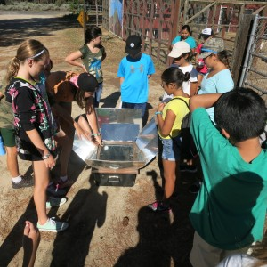 Students gathered around to witness the cooking power of the sun.